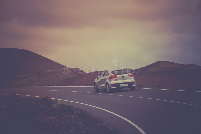 Wegweg met lijn in Timanfaya, Lanzarote spanje Witte auto op de weg Manier aan vulkaan Uitstekende retro Stijl royalty-vrije stock fotografie