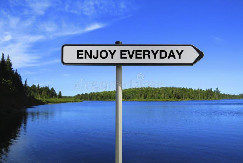 Wegweiserdienst mit ENJOY Jeden Tag Text unter blauem Seeufer-Hintergrund lizenzfreie stockfotografie