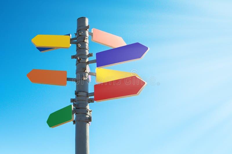 Wegwijzer met pijlen in het zonlicht tegen blauwe hemel stock foto