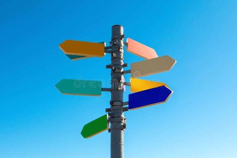 Wegwijzer met pijlen tegen blauwe hemel stock foto's