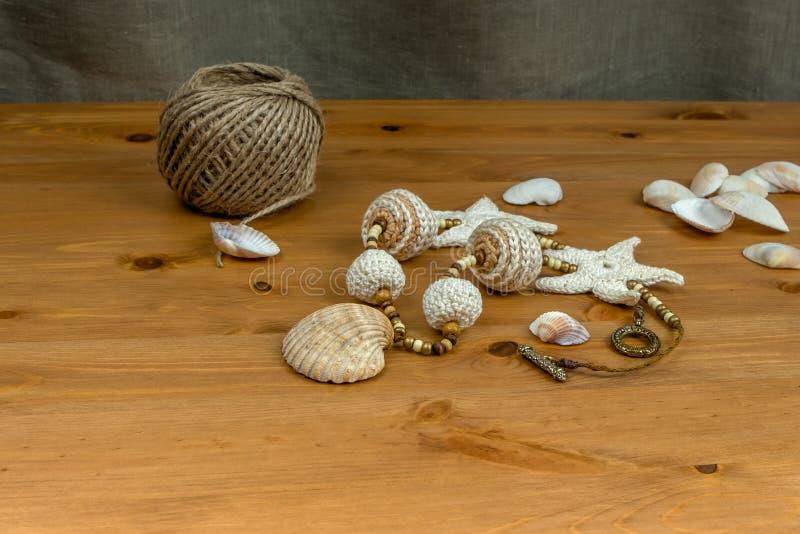 Weiß-beige Perlen der Häkelarbeit mit den natürlichen Muscheln hängend lizenzfreie stockfotos