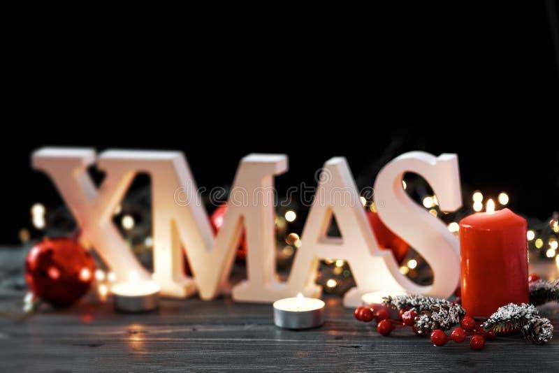 Weiß beschriftet Weihnachten auf Weihnachtsdekorationshintergrund Brennende Kerzen, Feiertagskranz auf einem bokeh Licht lizenzfreie stockfotos