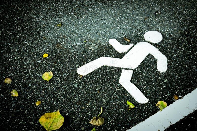 Weiß gemaltes Zeichen auf Asphalt Fußgängerweg und Gelbe trocknen Blätter stockfotografie