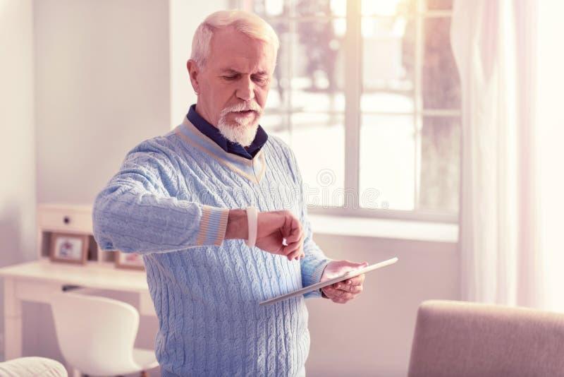 Weiß-haariger ernster Mann, der Zeit auf Uhr überprüft lizenzfreies stockfoto