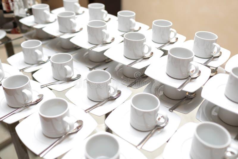 Weiß, Porzellanteeschalen auf einer weißen Untertasse mit einem silbernen Teelöffel auf einem Glastisch stockfoto