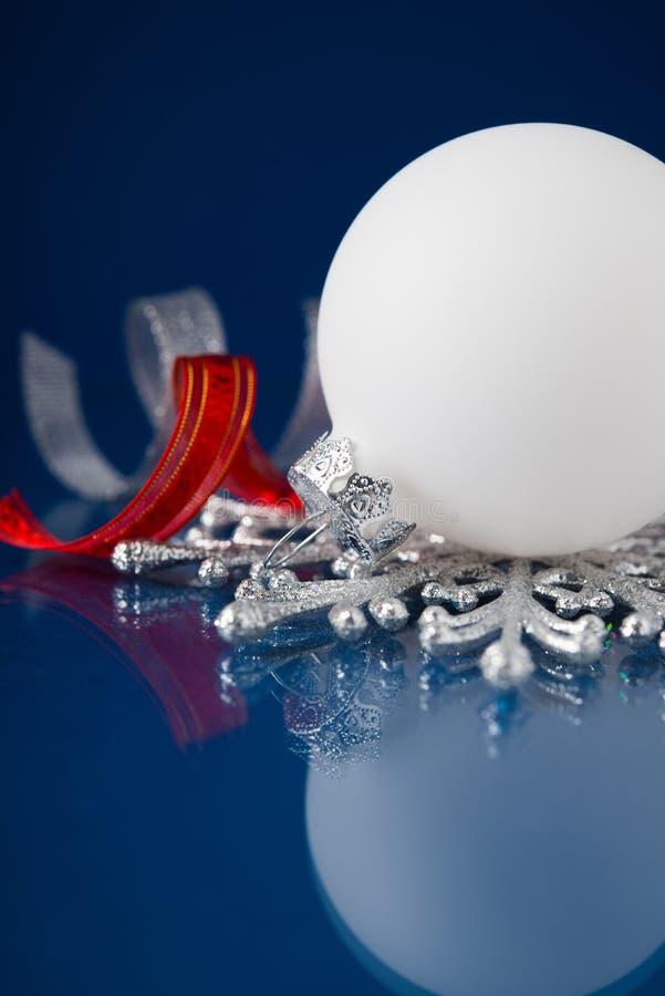 Weiß, Silber und rote Weihnachtsverzierungen auf dunkelblauem Hintergrund lizenzfreie stockbilder