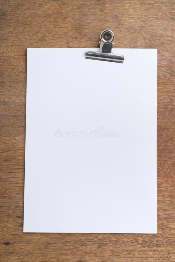 Weißbuch mit Papierklammer auf einer hölzernen Tabelle lizenzfreies stockbild