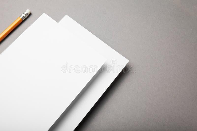 Weißbuch und Bleistift auf einem grauen Hintergrund lizenzfreie stockfotografie