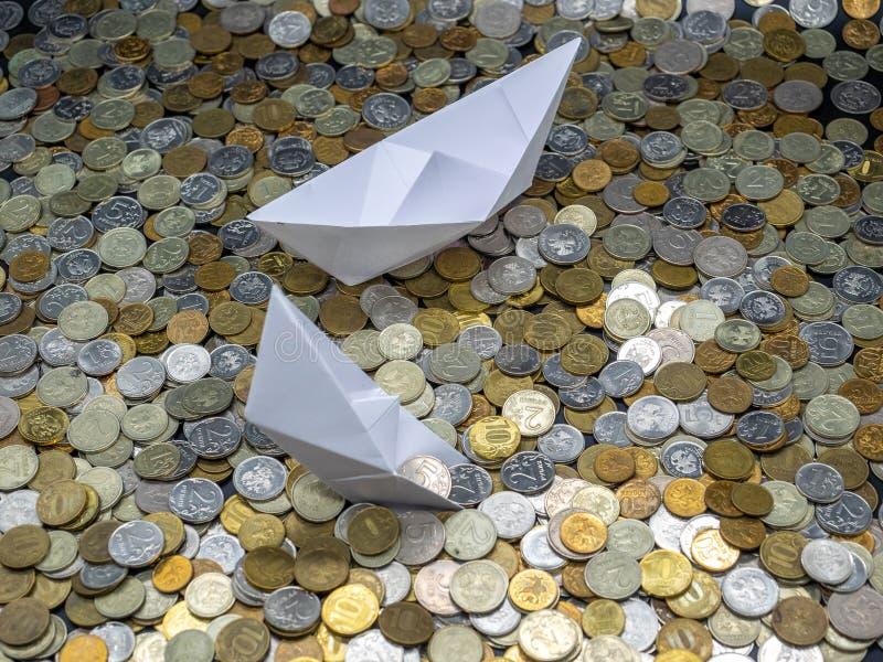 Wei?buchboote im Meer gemacht von den M?nzen: Segeln und Sinken stockfoto
