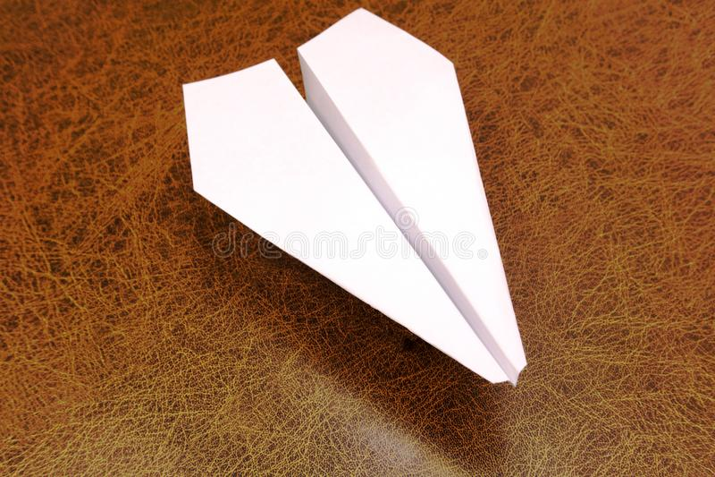 Weißbuchflugzeug durchbohrt mit einem Dolch auf einem rauen hölzernen Schild stockfotografie