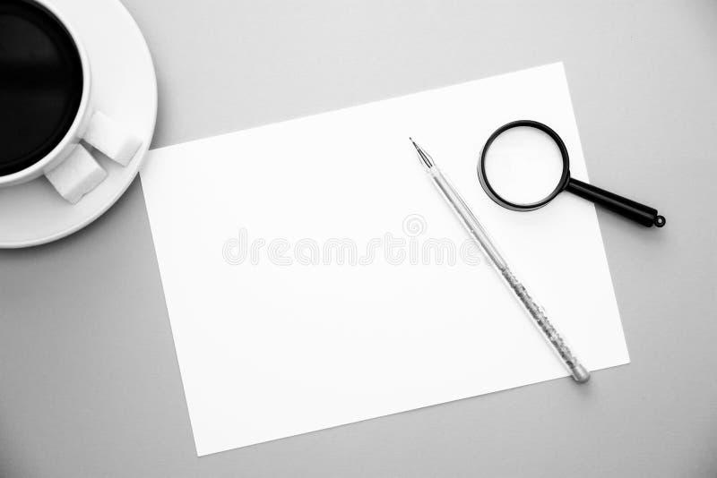 Weißbuchvergrößerungsglas des Stiftes und Kaffeetasse auf gelbem Hintergrund mit Draufsicht-Schwarzweiss-Bild des Kopienraumes lizenzfreies stockbild