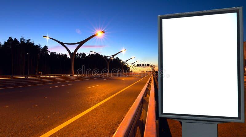 Weiße Anschlagtafel auf Beleuchtungslandstraße lizenzfreie stockfotografie