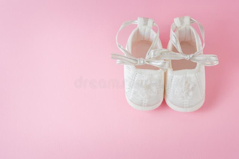 Weiße Babyschuhe auf rosa Hintergrund lizenzfreie stockbilder