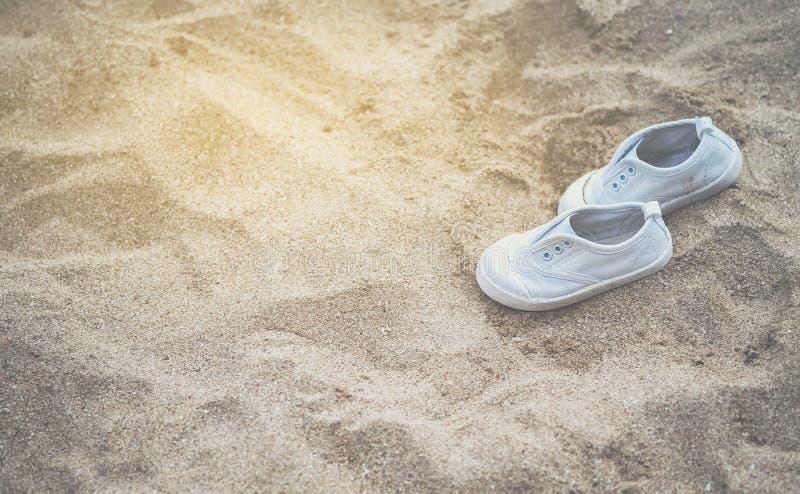 Weiße Babyturnschuhe auf dem sandigen Strand stockbild