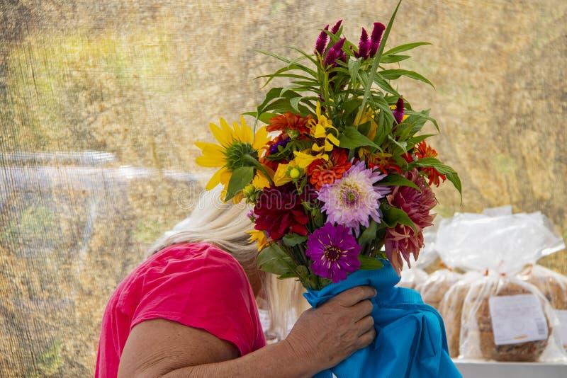 Weiße behaarte Frau kauft für Brot mit dem Gesicht, das durch ein enormes boquet von schönen bunten Blumen mit unscharfem Hinterg stockfotografie