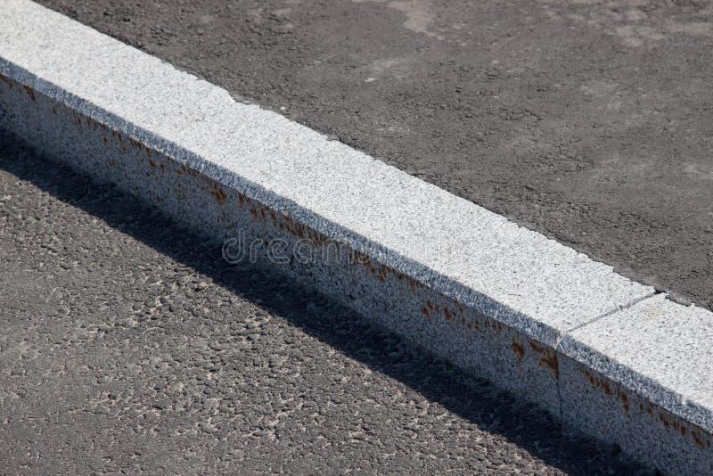 Weiße Beschränkung und Asphaltstraße stockbilder