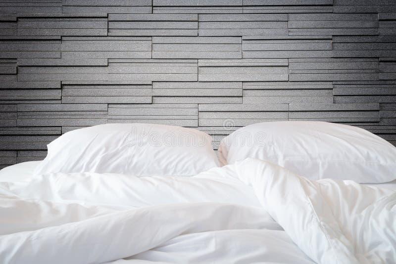 Weiße Bettwäscheblätter und -kissen auf Natursteinwand-Raum backg stockfotos