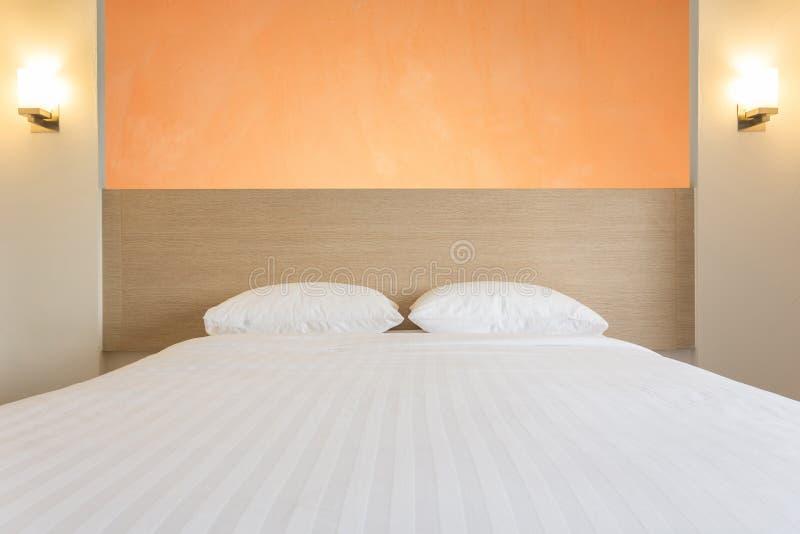 Weiße Bettwäscheblätter und -kissen im Hotelzimmer stockfotografie
