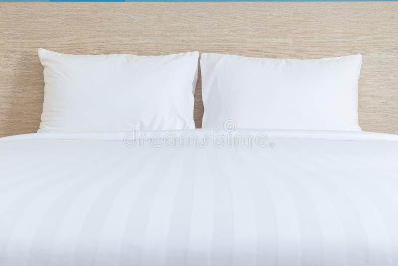 Weiße Bettwäscheblätter und -kissen im Hotelzimmer stockfoto