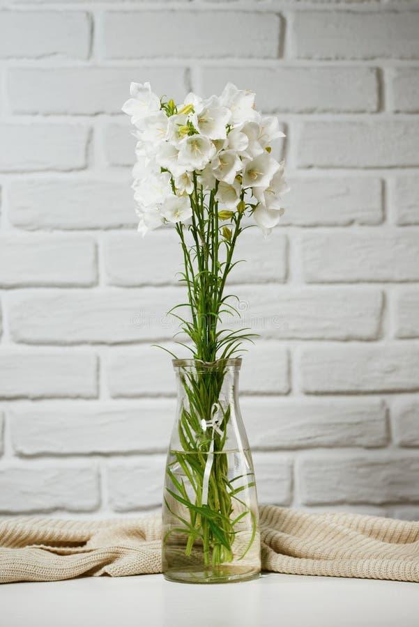Weiße Blume in einem Vase ist auf dem Tisch mit dem Stricken woolen, Backsteinmauerhintergrund stockbild