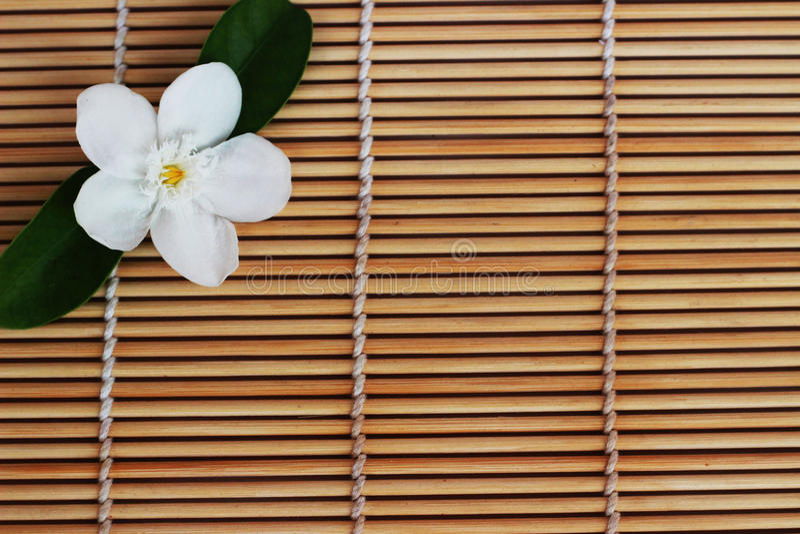 Weiße Blumen der Gardenie gesetzt auf braunen Webartbambus als backgroun stockfotografie