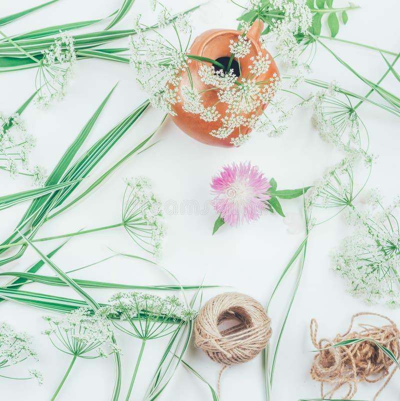 Weiße Blumen in einem Lehmpitcher, in der Blumenkornblume, in einem Seil und im dekorativen Gras der falaris auf einer Tabelle lizenzfreie stockfotografie