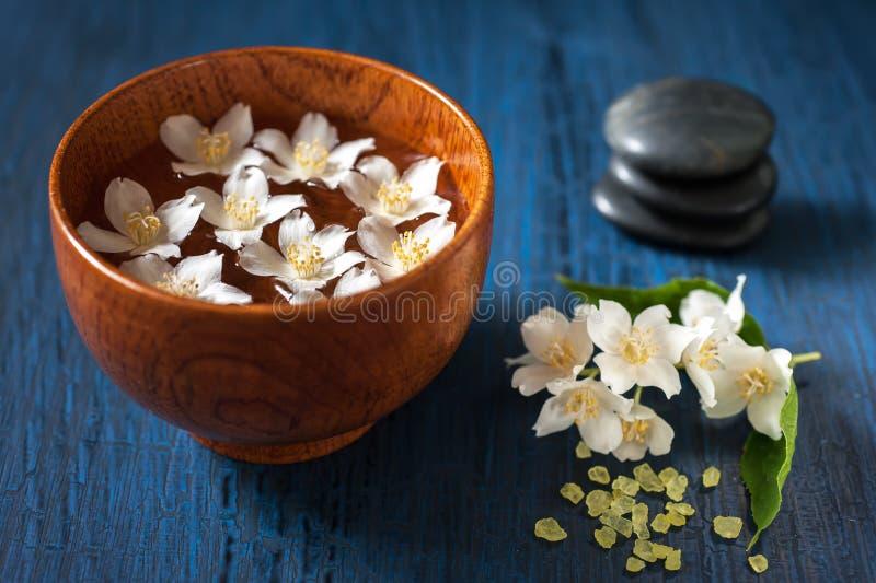 Weiße Blumen in einer Schüssel, Steine für Massage und Seesalz. Badekurortzusammensetzung. lizenzfreie stockfotografie