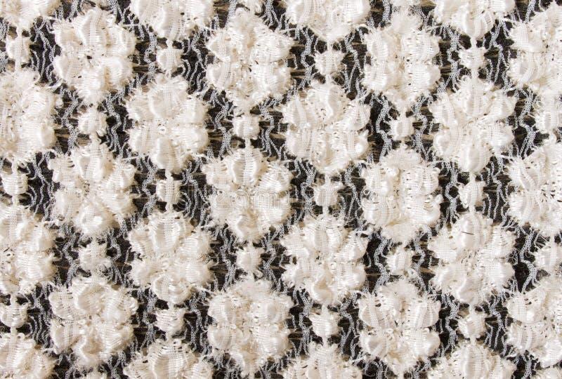 Weiße Blumen-strickendes Muster auf schwarzem Gewebe-Beschaffenheits-Hintergrund lizenzfreie stockfotografie