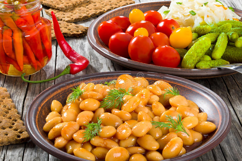 Weiße Bohnen, in Essig eingelegter Kohl, Kirschtomaten, Gurken, Paprika stockbild