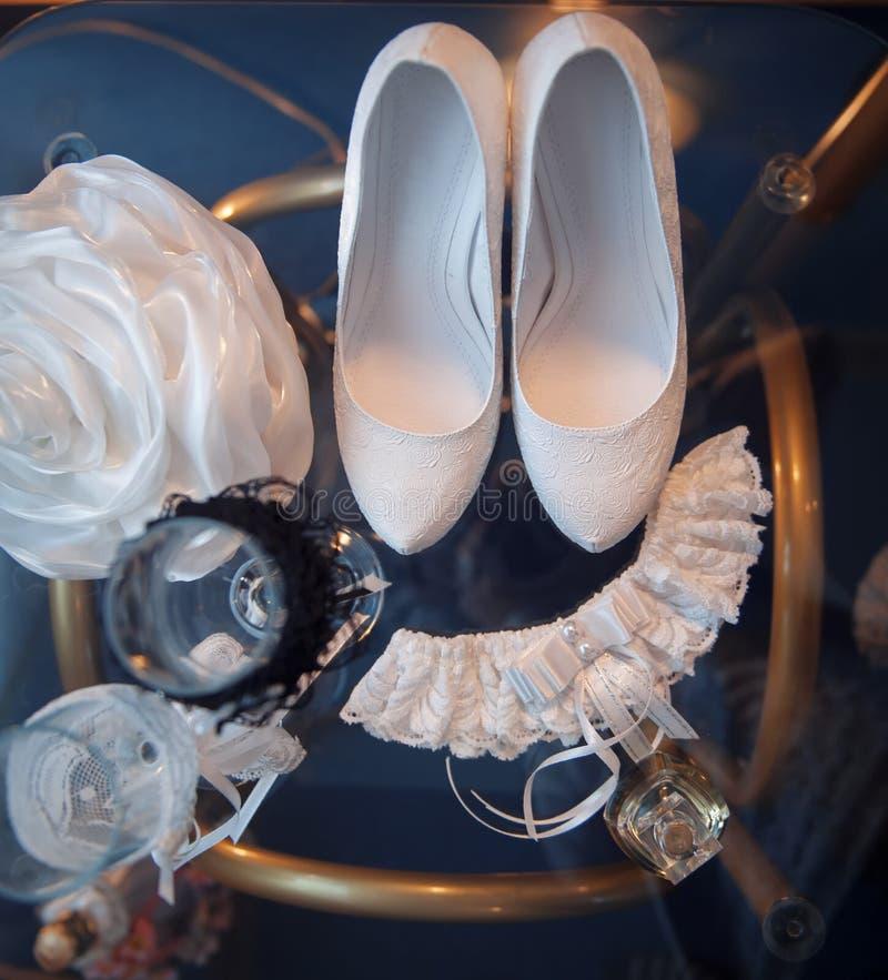 Weiße Brautschuhe und andere Hochzeitsattribute auf einer Tabelle stockfotografie