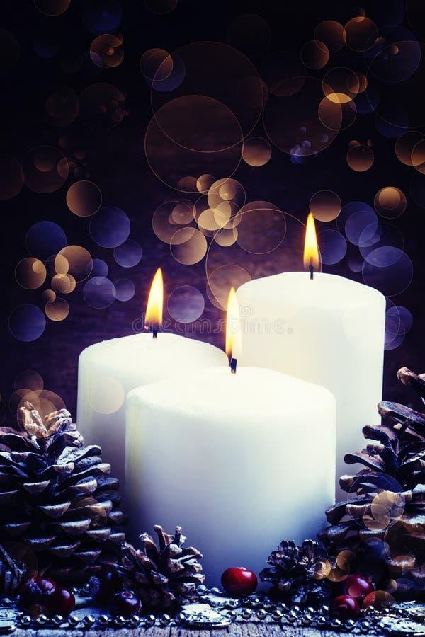 Weiße brennende Kerze mit Kiefernkegeln und Moosbeeren, Weihnachten lizenzfreie stockfotos