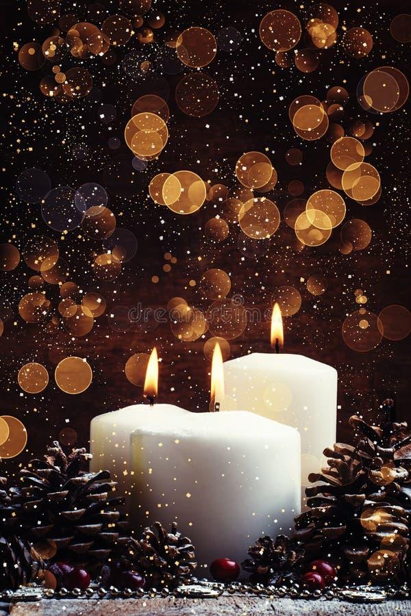 Weiße brennende Kerze mit Kiefernkegeln und Moosbeeren, Weihnachten stockfoto