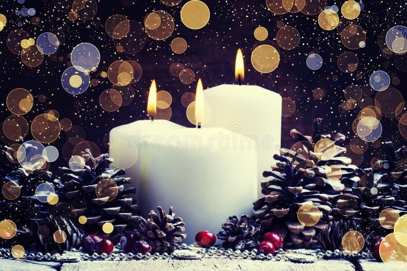 Weiße brennende Kerze mit Kiefernkegeln und Moosbeeren, Weihnachten stockfotografie