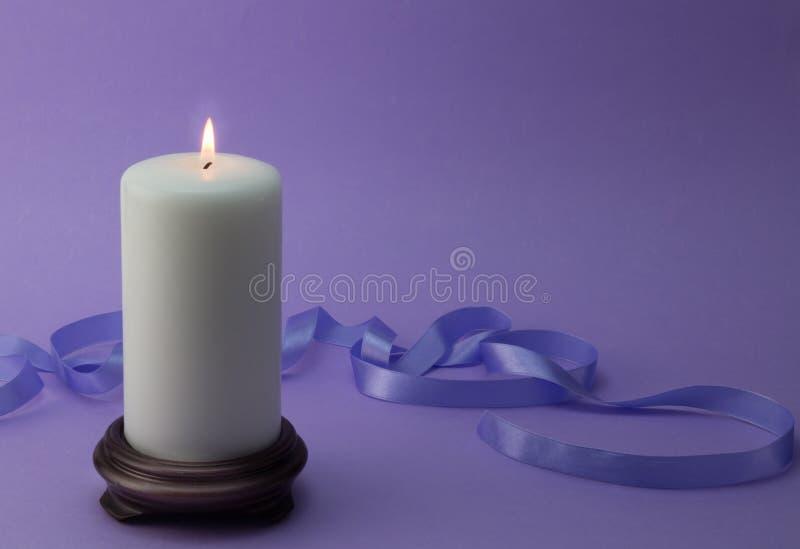 Weiße brennende Kerze mit lila Band und Hintergrund lizenzfreies stockfoto