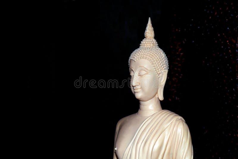 Weiße Buddha-Statue auf schwarzem Hintergrund, der Buddha wird von Elfenbein geschnitztem Weiß gemacht, das geschnitzte Elfenbein stockbild