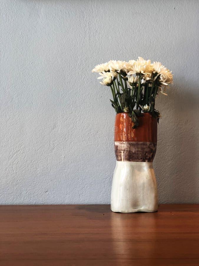 Weiße Chrysanthemenblume im schönen Vase auf dem Holztisch mit Zementhintergrund lizenzfreie stockfotografie