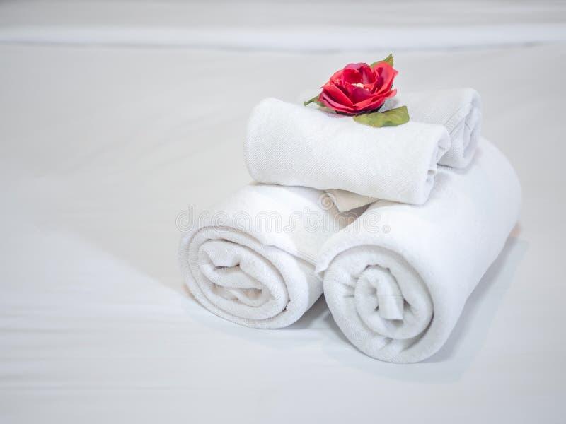 Weiße Dekoration der sauberen Tücher mit roter Blume auf weißem sauberem Bett im Hotelzimmer lizenzfreie stockbilder