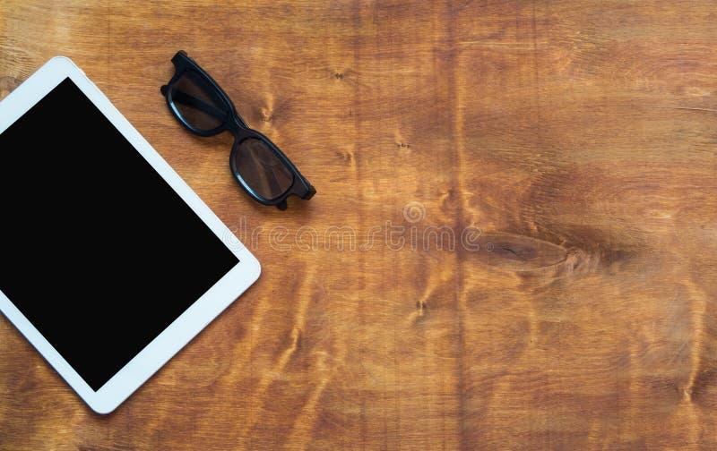 Weiße digitale Tablette mit schwarzem Schirm und schwarzen Gläsern auf hölzerner Tabelle Kopieren Sie Platz stockbilder