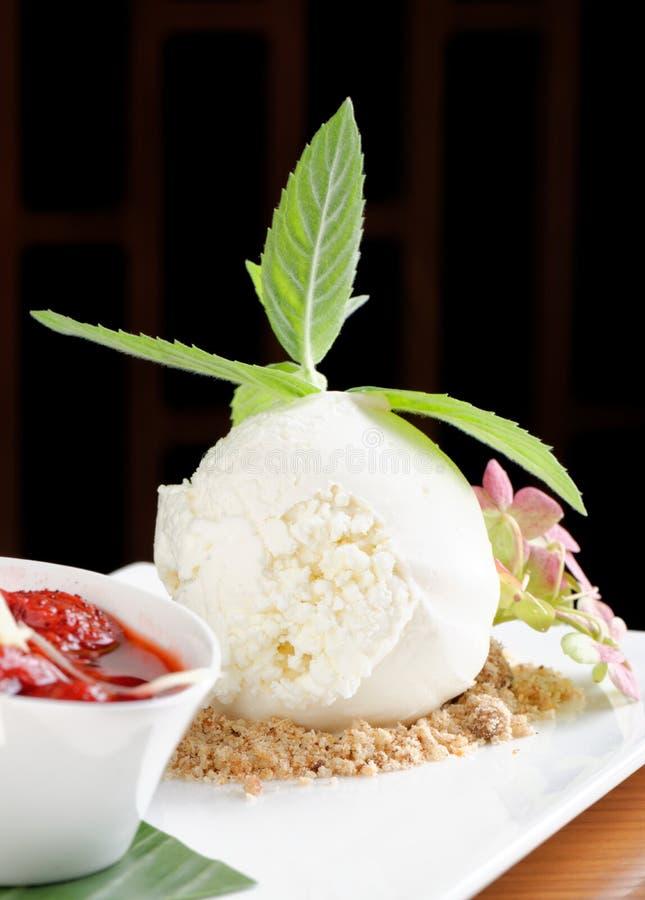 Weiße Eiscreme mit heißer Erdbeersoße lizenzfreies stockbild
