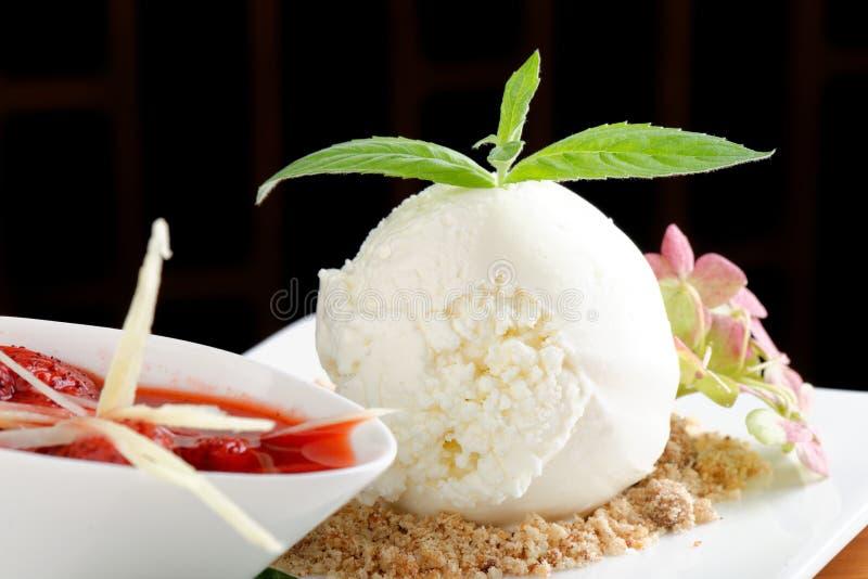 Weiße Eiscreme mit heißer Erdbeersoße lizenzfreie stockfotos