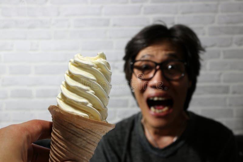 Weiße Eiscreme-Spiralenform auf der Schaufel in der Hand und fokussieren heraus den aufgeregten Mann, möchten essen lizenzfreie stockbilder