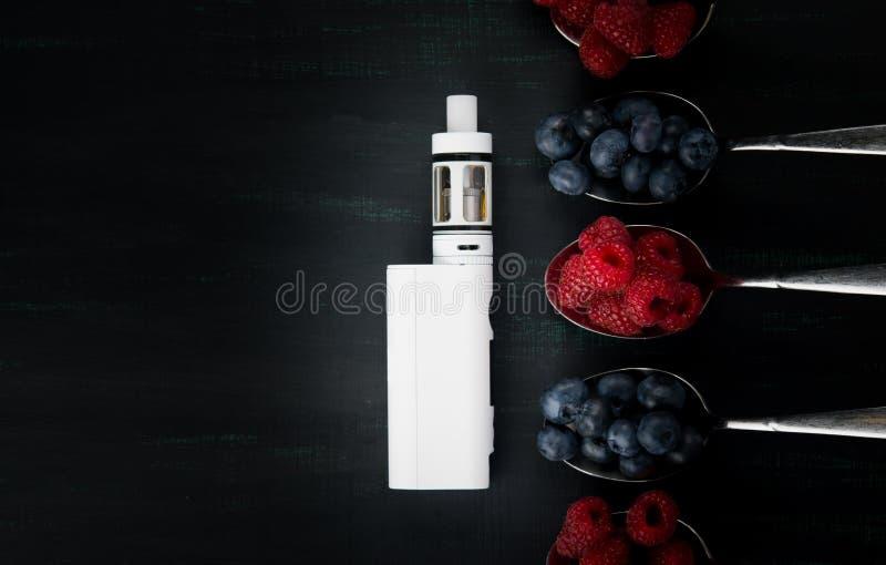 Weiße elektronische Zigarette auf einem schwarzen Hintergrund, mit verschiedenen Aromen von Beeren auf ihm lizenzfreies stockfoto