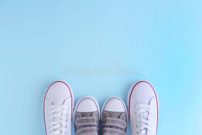Weiße Erwachsener und Kindersneackers auf blauem Hintergrund stockfoto