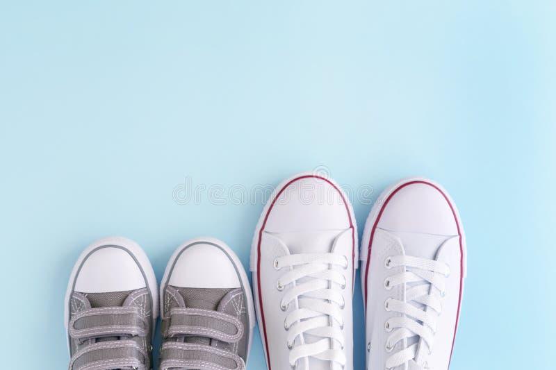 Weiße Erwachsener und Kindersneackers auf blauem Hintergrund stockfotos