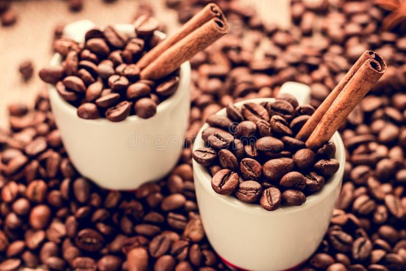 Weiße Espressoschalen mit Kaffeebohnen und Zimtstangen stockfoto
