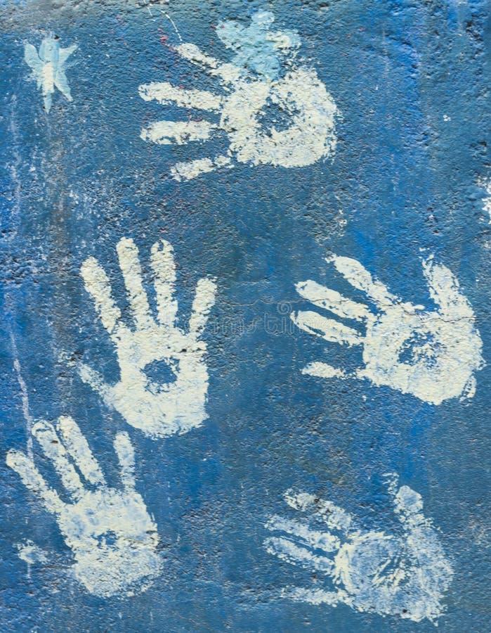 Weiße Farbe handprints auf einer Himmelblauwand stockfotos
