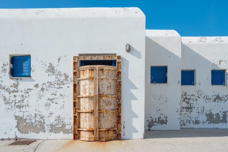Weiße Fassade des Dockgebäudes mit traditionellen blauen Fenstern und der alten rostigen Tür auf Andros-Insel, Griechenland stockfoto