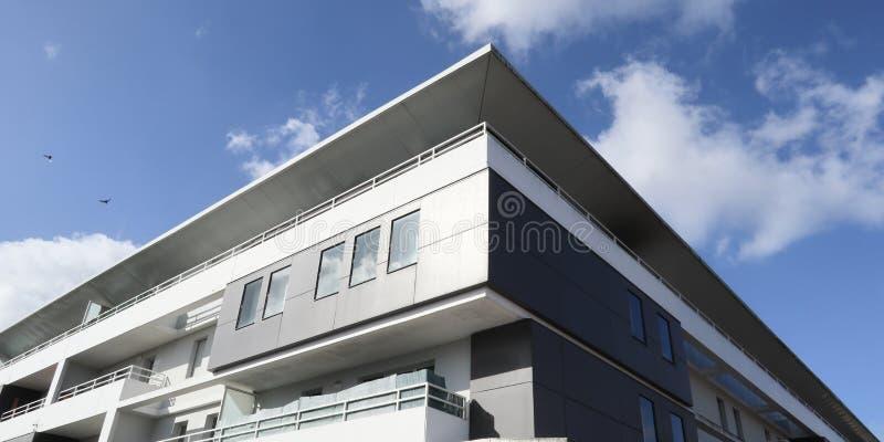 Weiße Fassade eines modernen Wohngebäudes mit Fenstern und verschiedenen schwarzen Akzenten stockfotos
