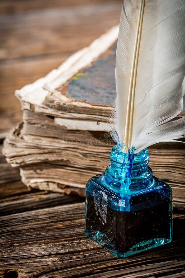Weiße Feder auf blauem Tintenfaß und altem Buch stockbilder