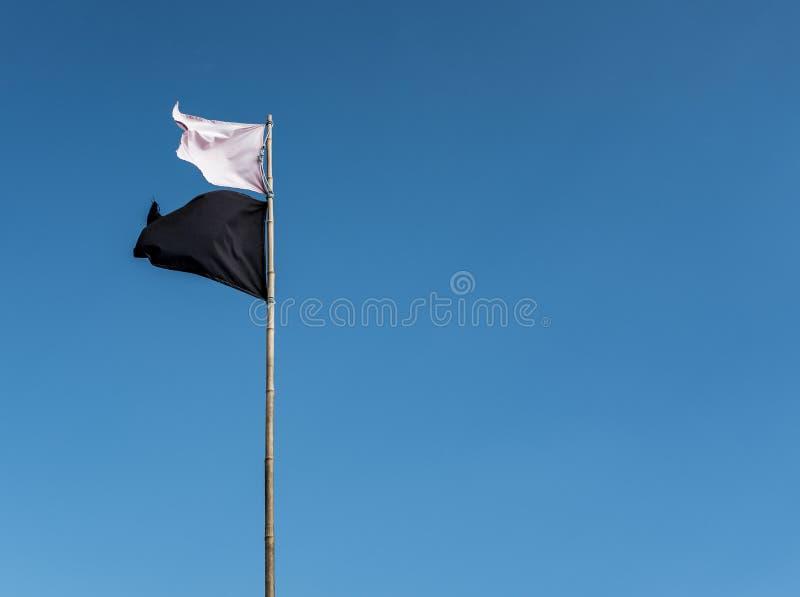 Weiße Flagge und eine schwarze Flagge, die auf einen hohen Metallpfosten mit einem klaren blauen Himmel im Hintergrund wellenarti stockfoto